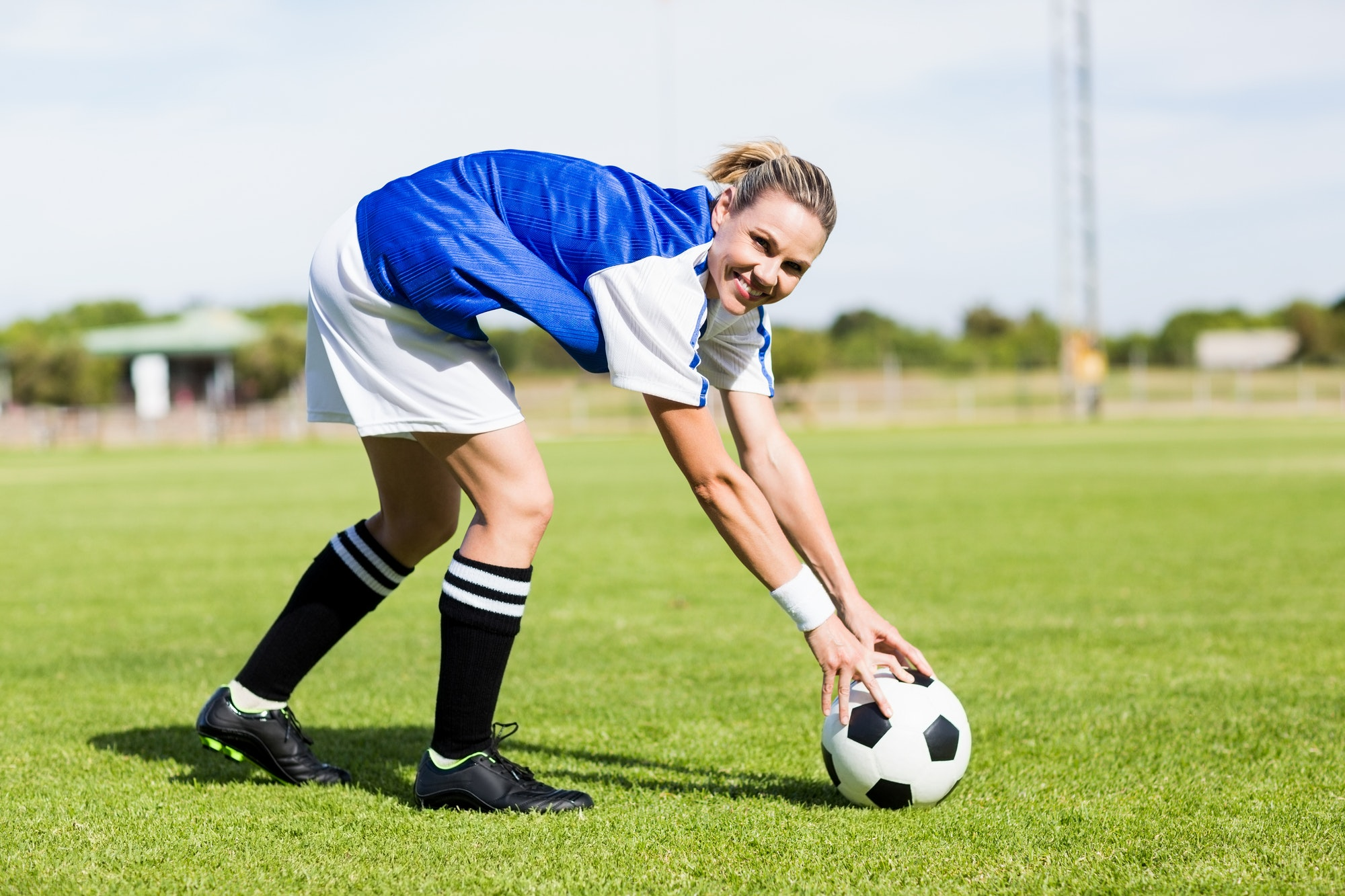 Portrait of female football player keeping a ball